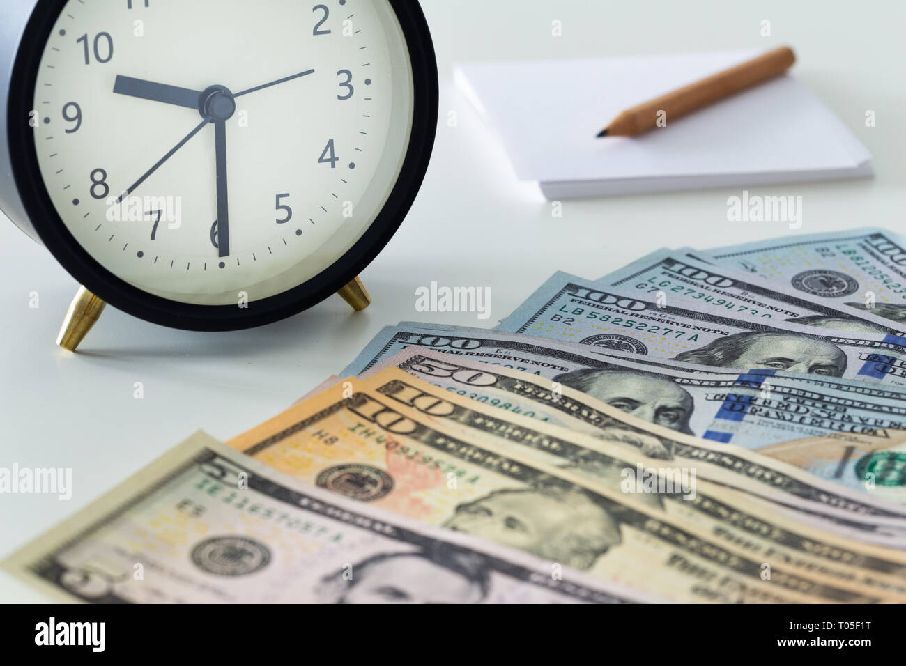 American dollars with an alarm clock, a page and a pencil - Stock Image