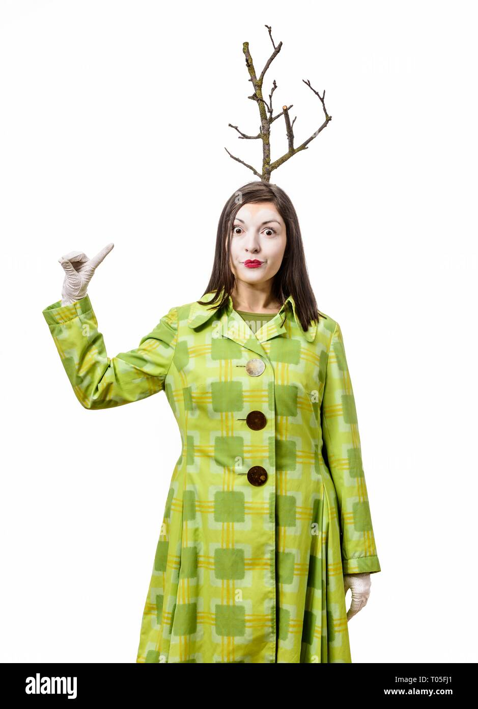 Shocked clown standing in suit and gesturing on white background. A branch grows from his head. Pointing with your finger up. - Stock Image