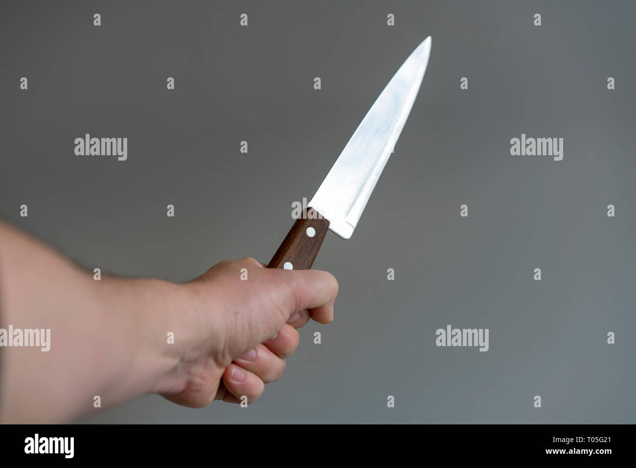 Man's hand with a knife on gray background. Concept of violence. Stock Photo