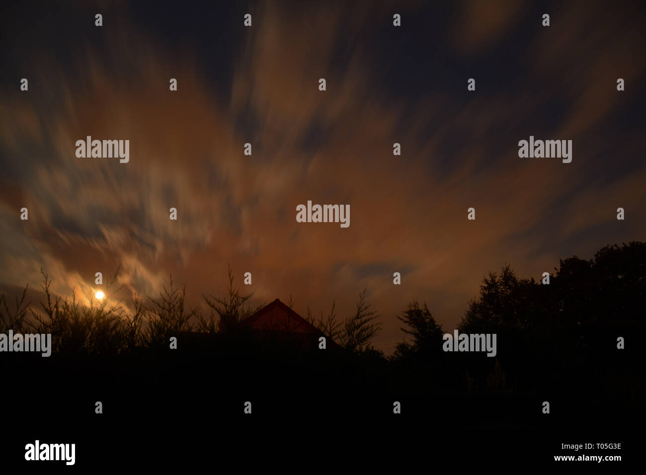 The blood moon illuminates the clouds in the late evening - Stock Image