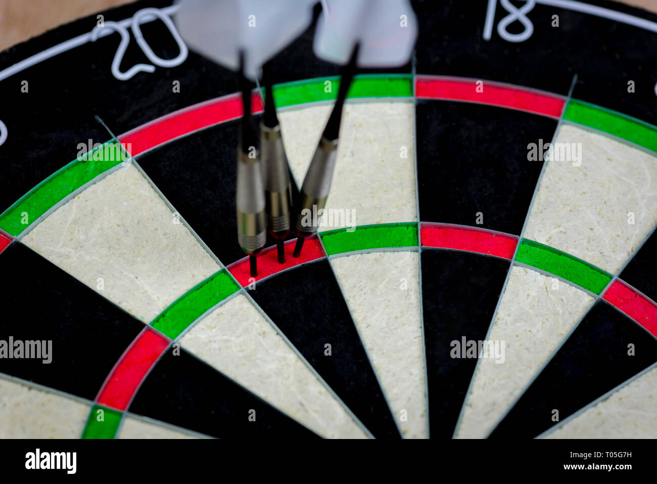 dart board with three darts in the triple twenty area. - Stock Image