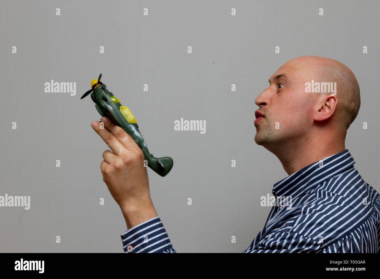 man holding a paper airplane and dreaming aboyt flying on a gray background Stock Photo