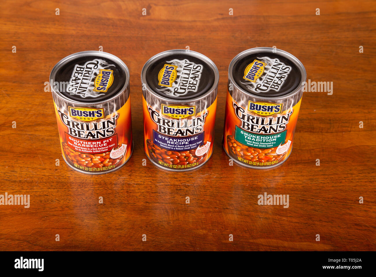 ATLANTA, GEORGIA - April 21, 2017: Bush's Grillin Beans. Three varieties of beans in cans on wood table. - Stock Image
