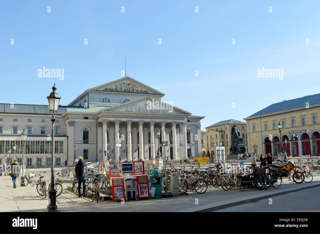 MUNICH, GERMANY - 25 FEBRUARY 2019:  Bicycles parked in winter sunshine on  Max-Joseph-Platz where a statue of Maximilian I stands in front of the Nat - Stock Image
