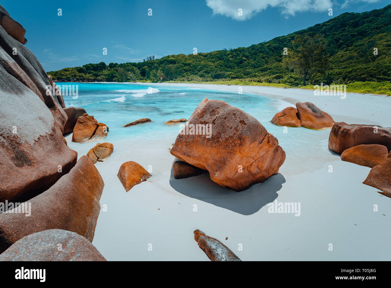 Tropical lagoon with granite boulders in the turquoise water and a pristine white sand at Anse Cocos, La Digue island, Seychelles Great location for r Stock Photo