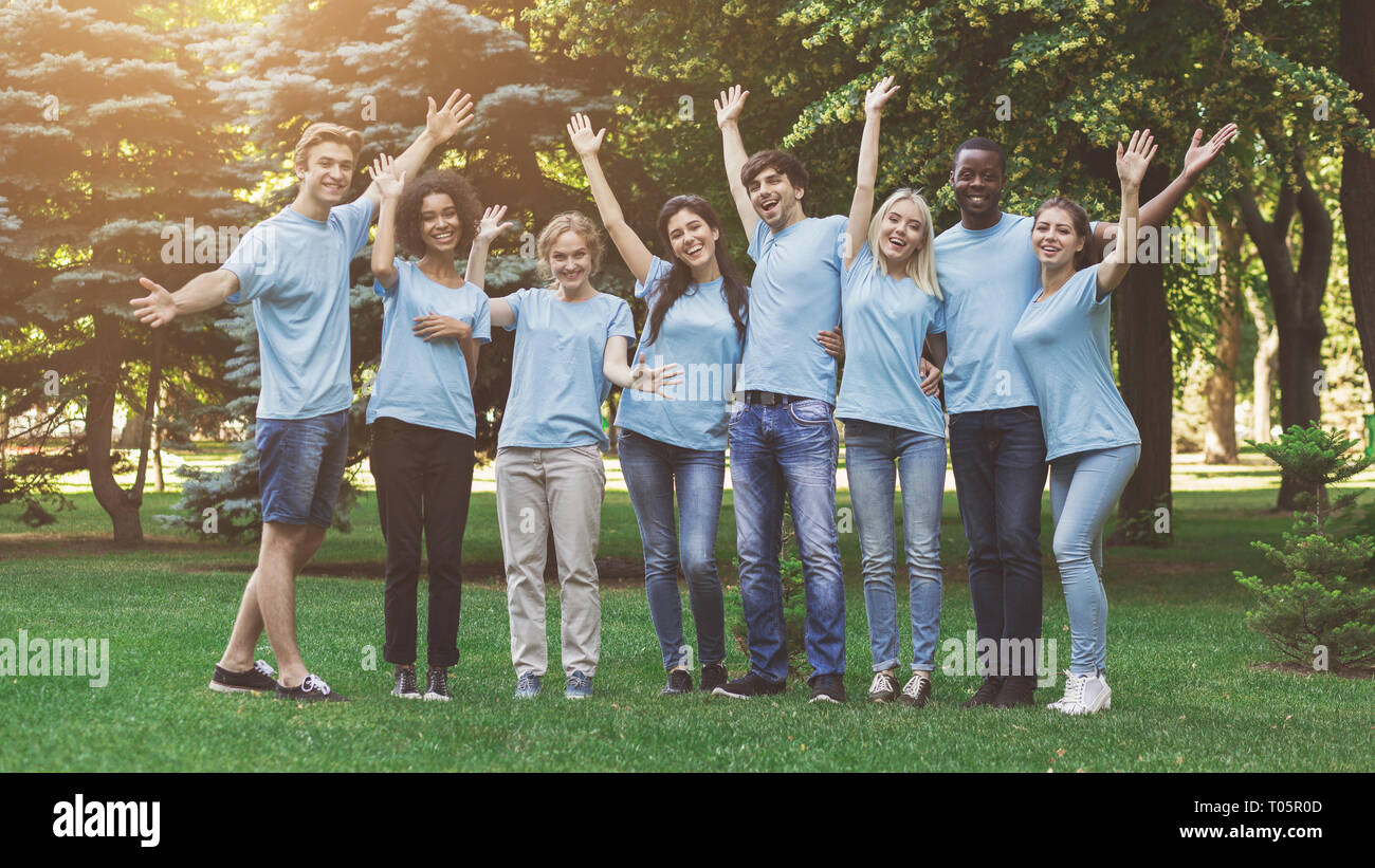 Group of young volunteers embracing at park - Stock Image
