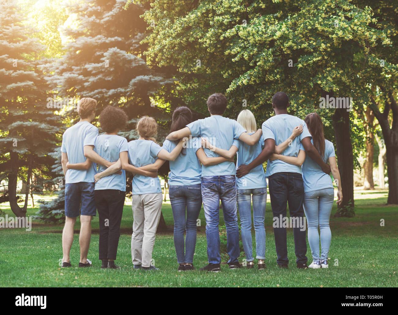 Group of happy volunteers embracing in park - Stock Image