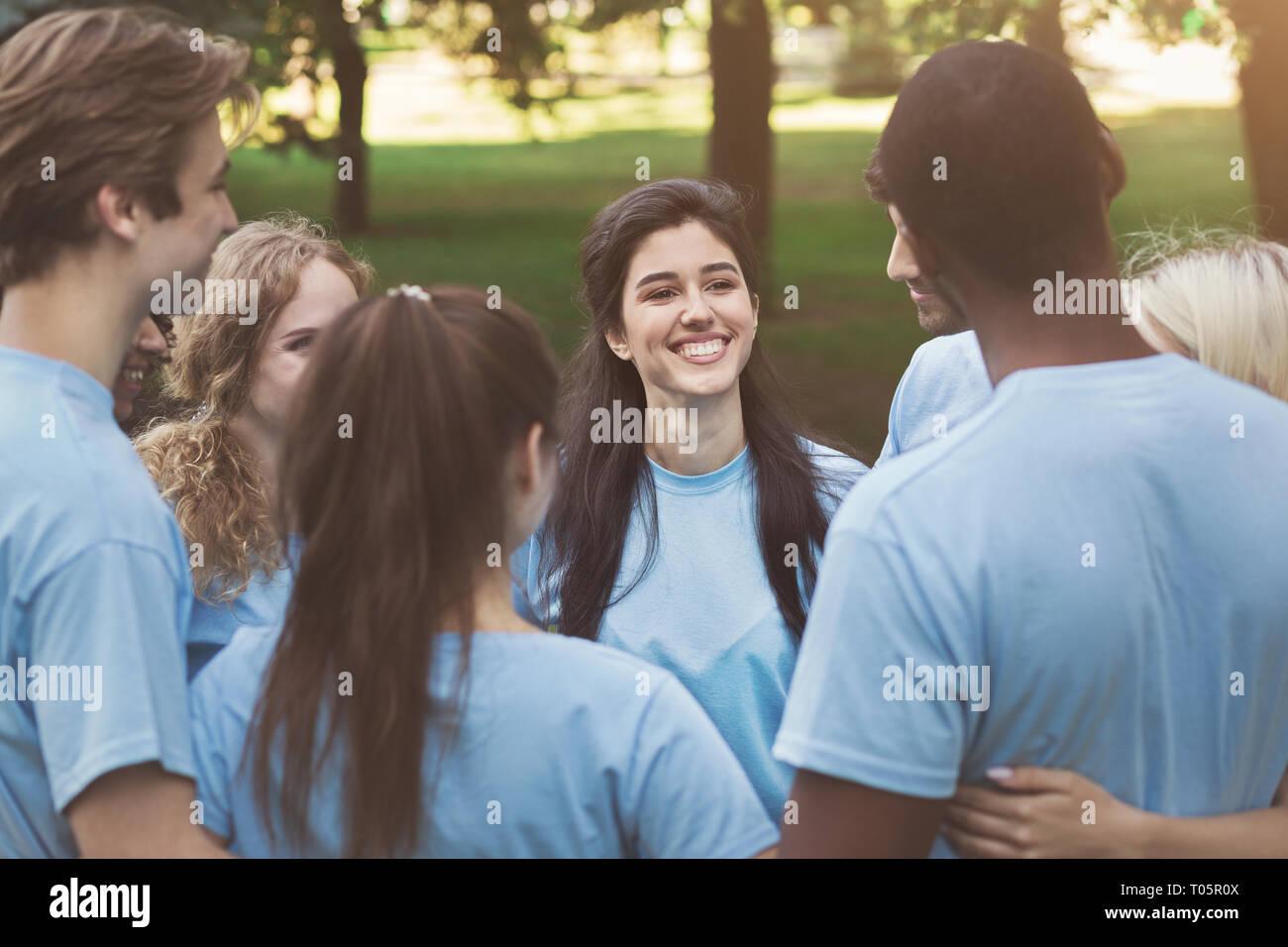 Meeting of young volunteers team in park - Stock Image