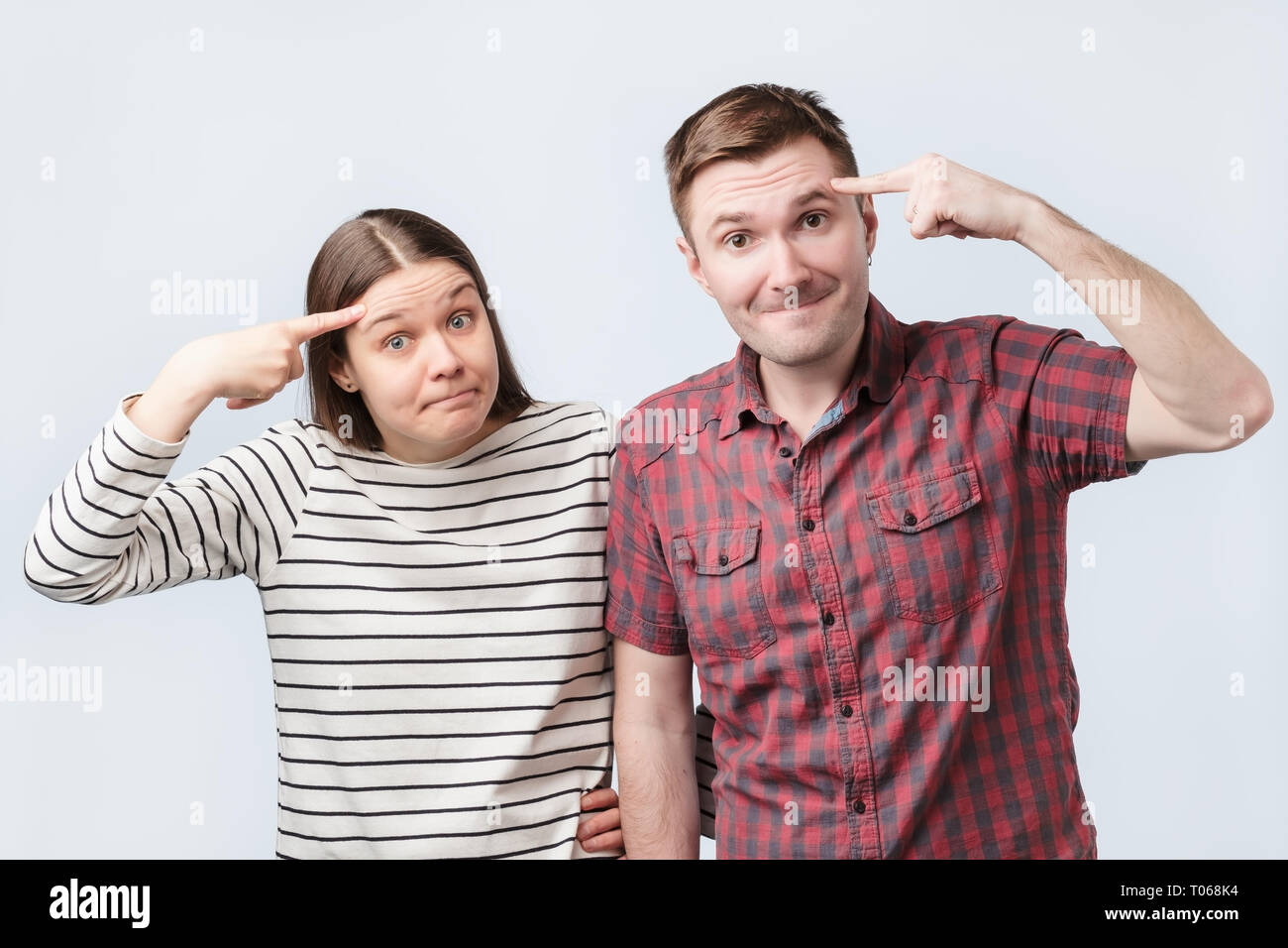 Funny young woman and man have dissatisfied facial expressions, keep index fingers on temples, - Stock Image