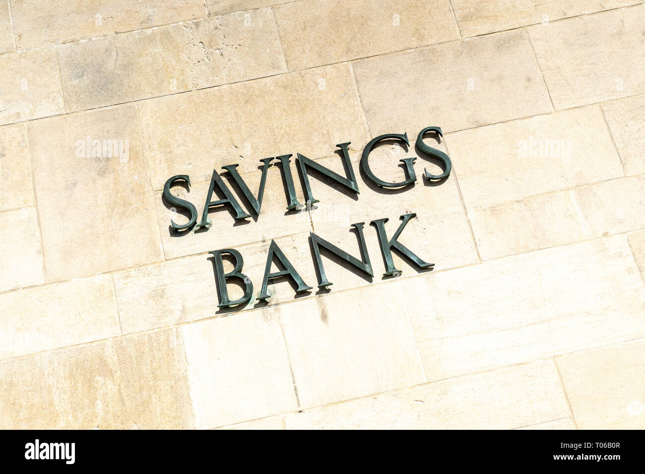 Savings Bank in metal letters on stone wall - Stock Image