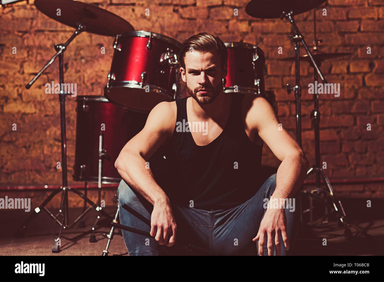 Theres music in the air. Enjoying instrumental music. Handsome man sit on stage at percussion instrument. Man drummer with musical instrument. Rock - Stock Image