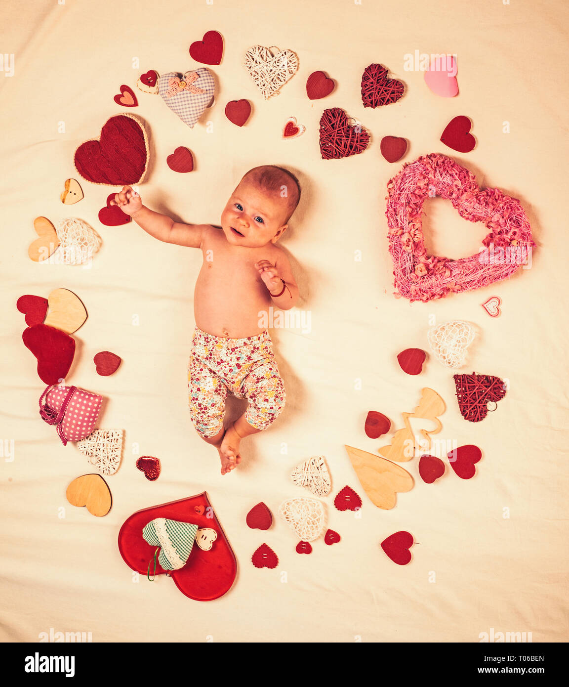 Pleasant timespending. Love. Portrait of happy little child. Sweet little baby. New life and birth. Family. Child care. Small girl among red hearts - Stock Image