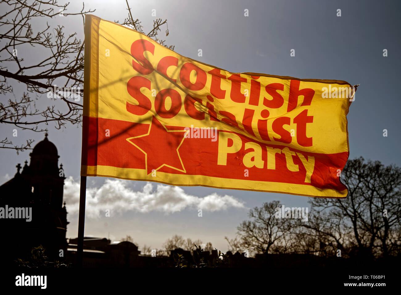 The sun shines through a Scottish Socialist Party flag on Princes Street, Edinburgh, Scotland, UK. - Stock Image