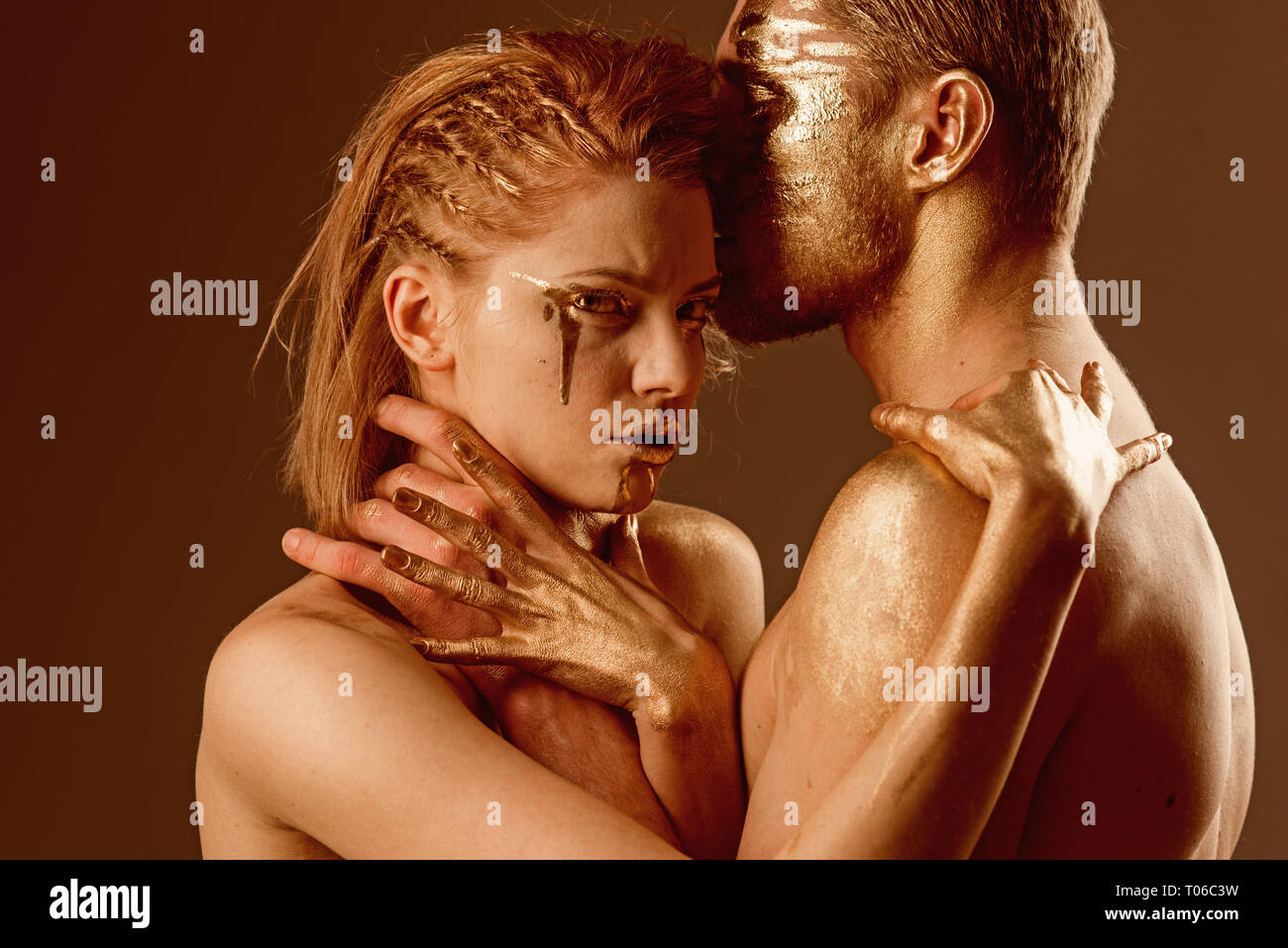 strangle concept. strangle of girl by man, both have golden paint on body. - Stock Image