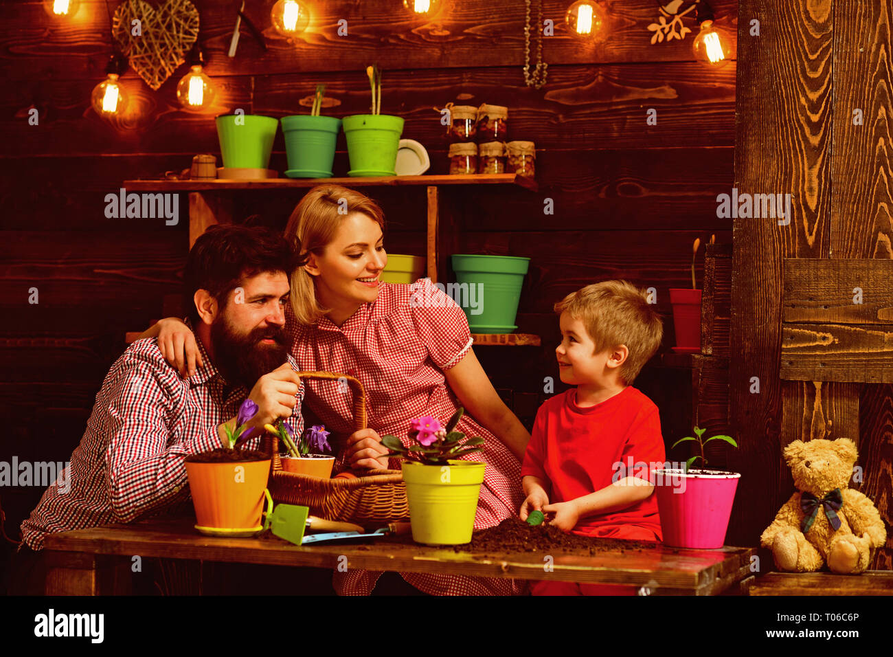 Decor concept. Little boy with woman and man planting flower in new pot decor. Home decor. Natural eco decor - Stock Image