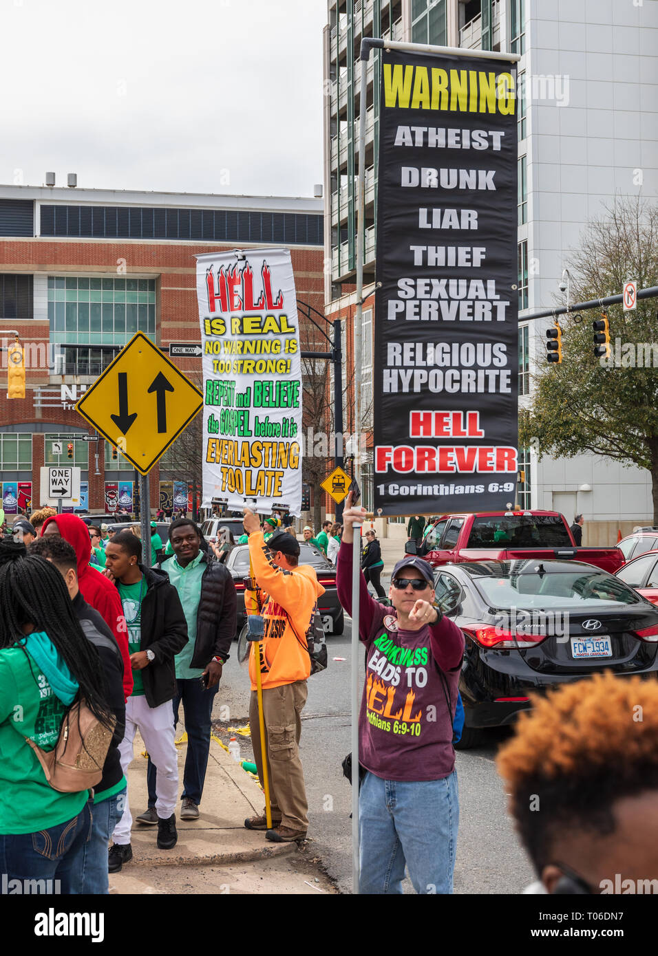 """CHARLOTTE, NC, USA-3/16/19: A man points at camera while holding a sign listing behaviors which mean """"Hell Forever"""". Stock Photo"""