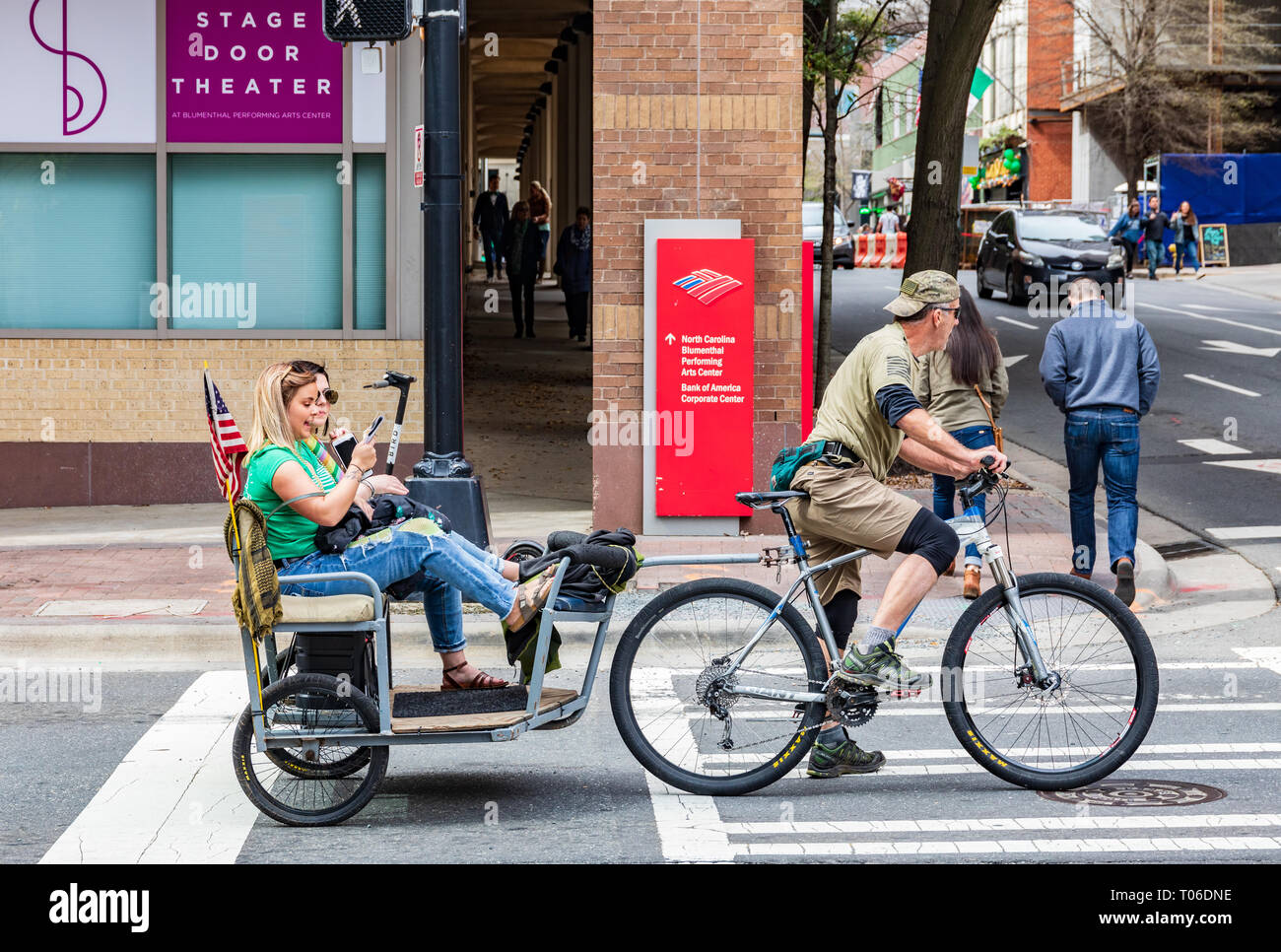 CHARLOTTE, NC, USA-3/16/19: Two young women look at smart phones while riding in a bicycle towed cart in uptown Charlotte. Stock Photo