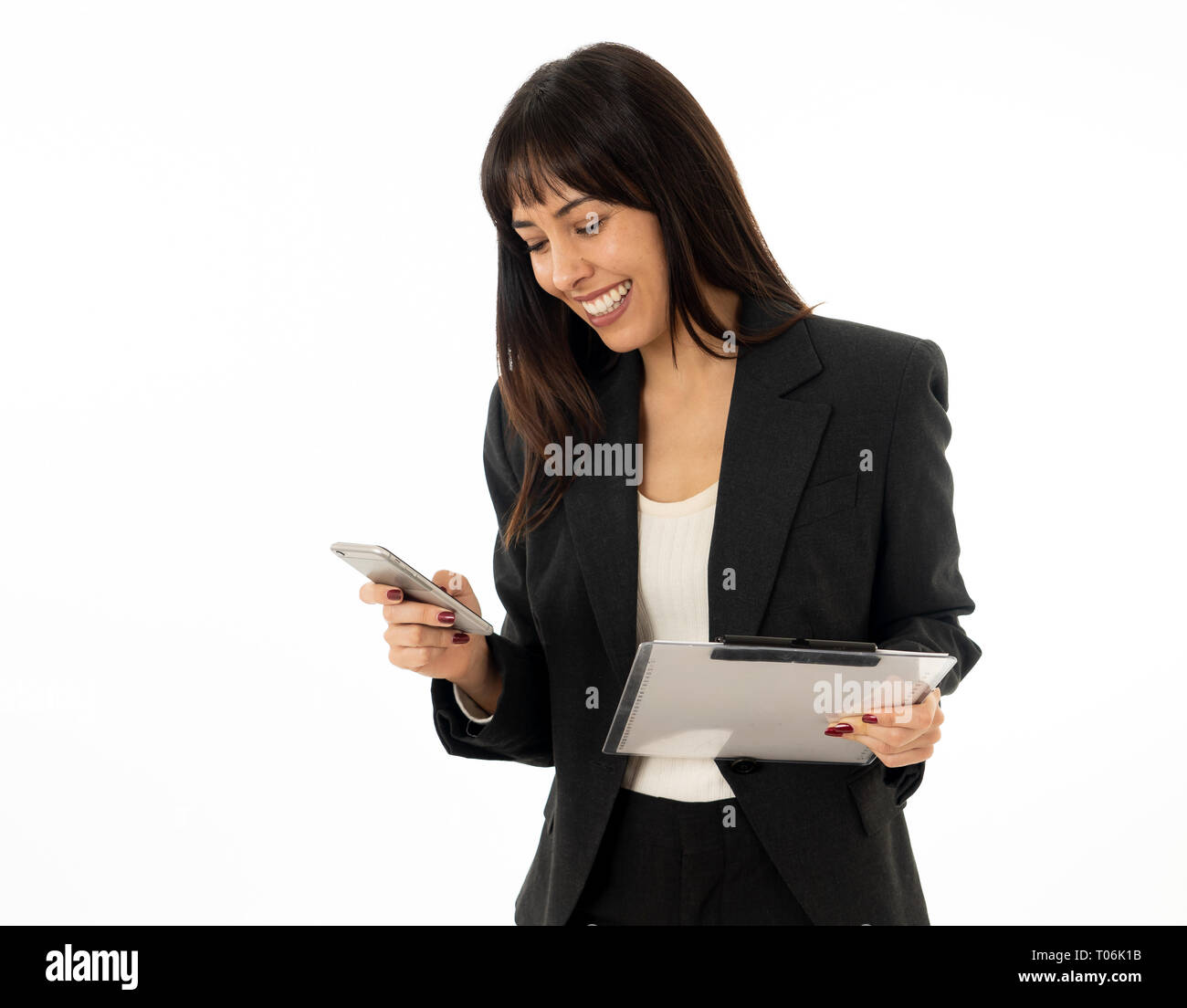Portrait of young beautiful successful businesswoman emailing and sending messages on mobile smart phone feeling confident at work. In people business - Stock Image