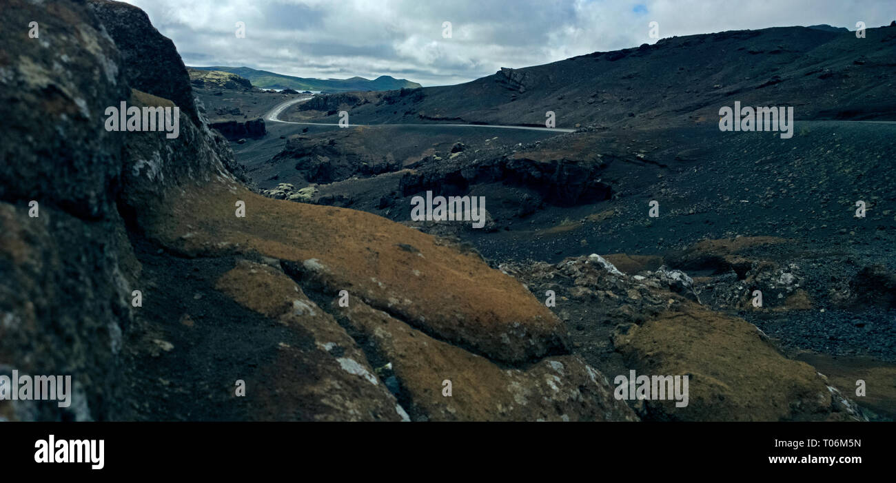stunning drone shots of an isolated road passes through a volcanic barren landscape in remote Iceland. Stock Photo