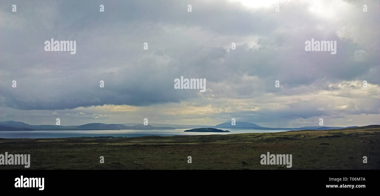 an Inland Lake and coastline roads in the volcanic landscape of central Iceland. A barren rugged lake shore is filled with volcanic rocks. Stock Photo