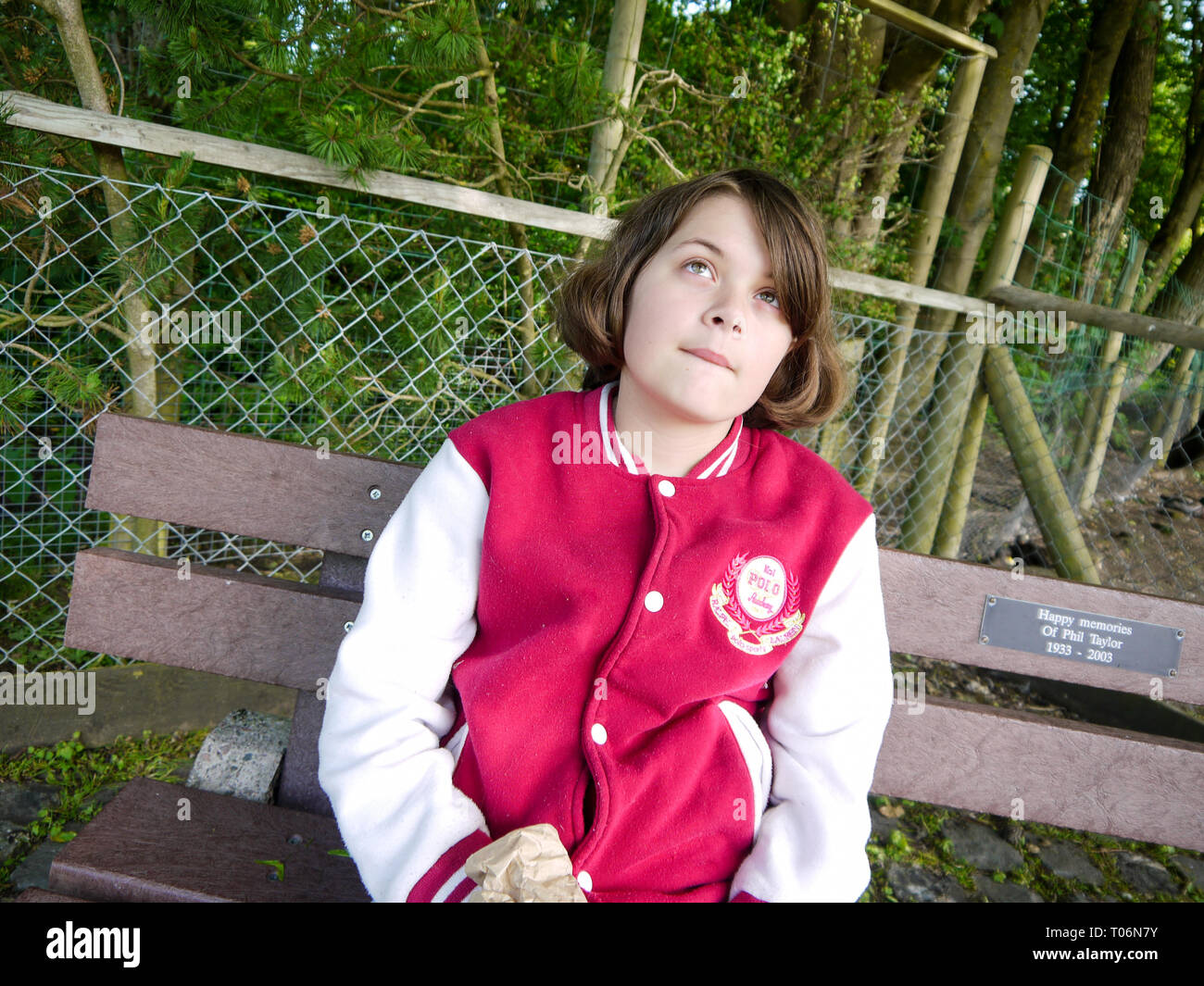 Young teenage girl sitting on a bench outdoors thinking / wondering / pondering - Stock Image