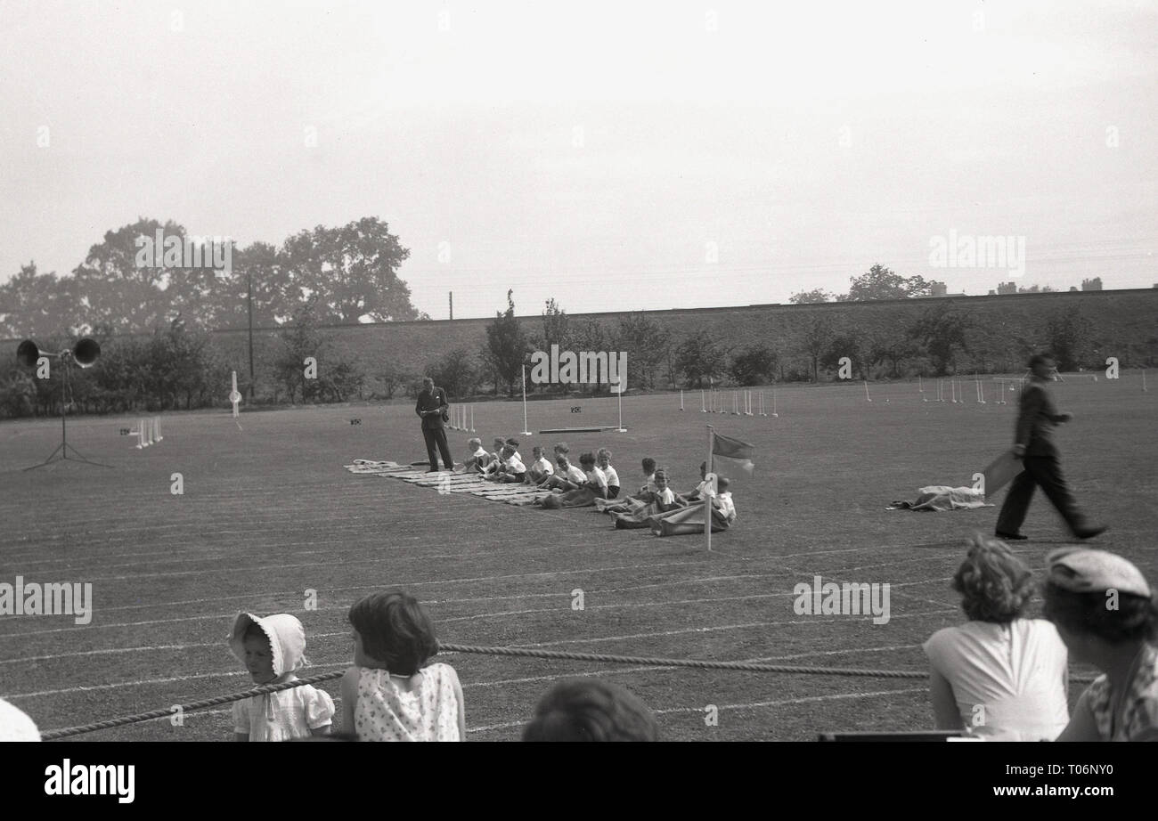 1950s, sack race, primary school, schoolboys sit outside on the sport field getting into their sacks, England, UK. - Stock Image