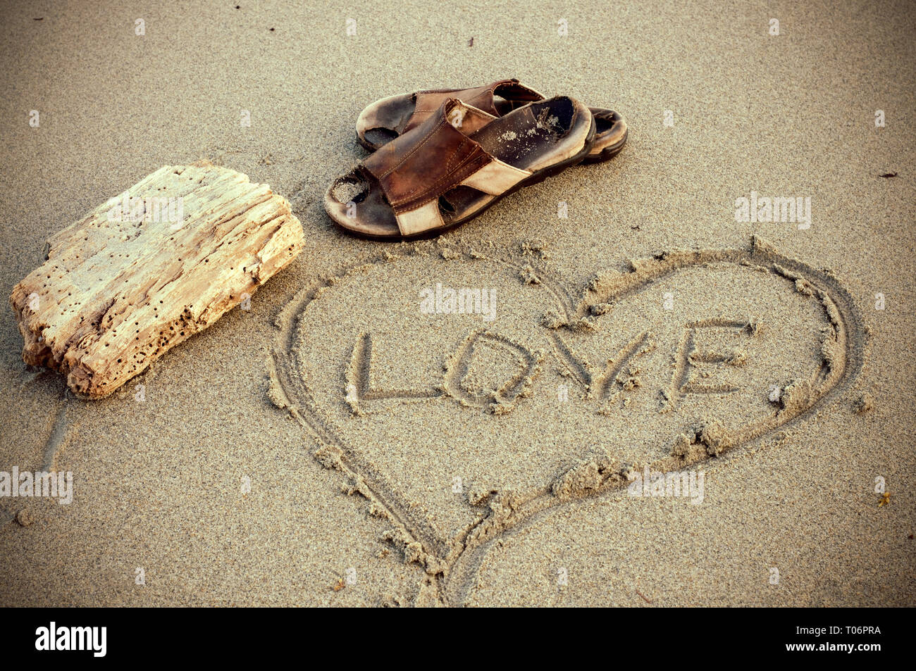 2042e8b82 Sepia Colored Old Sandals with Love Heart Drawn in the Beach Sand ...