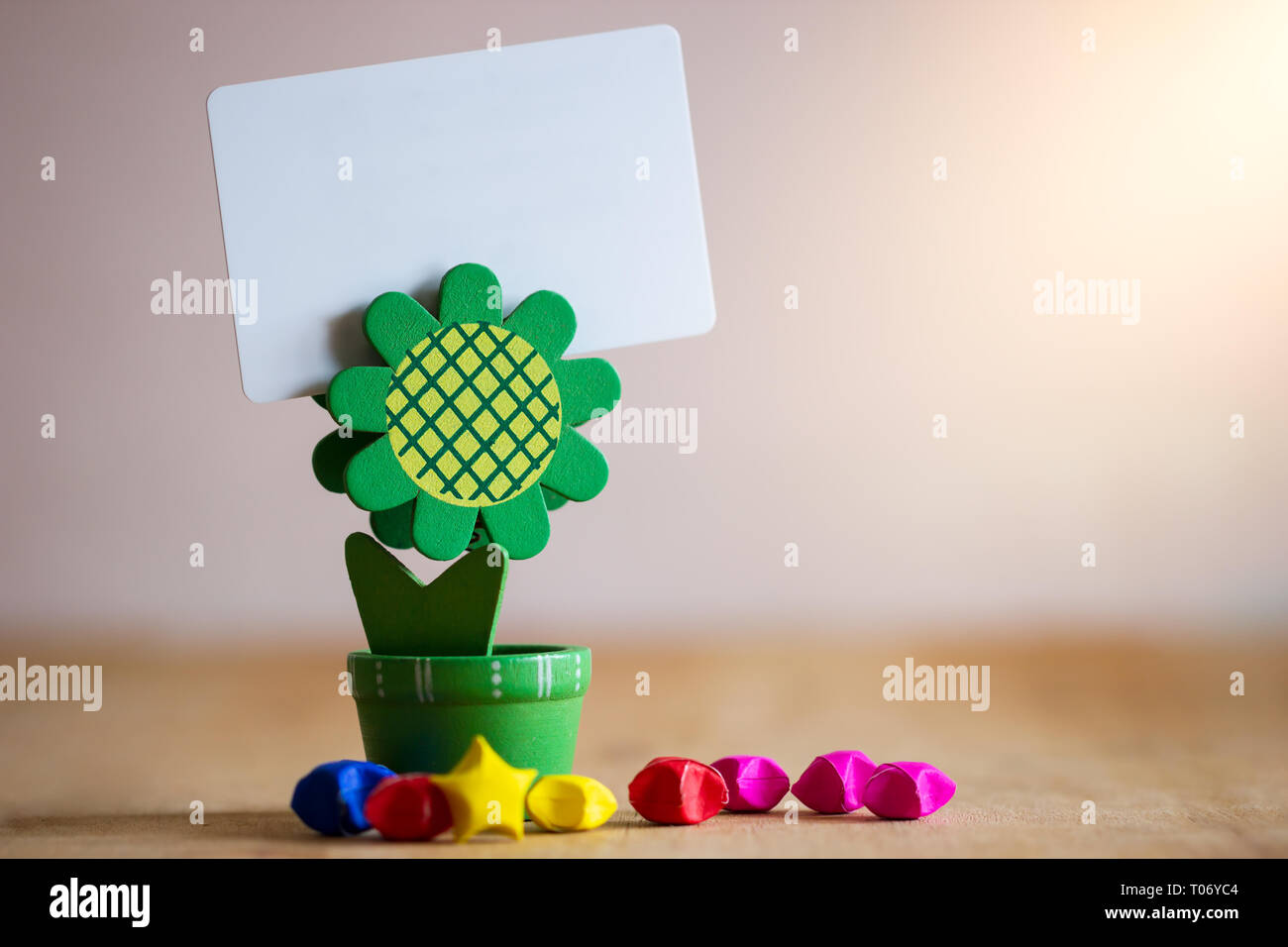 Clip holder card stand green sunflower shaped and multicolored paper stars on wooden table. White plastic blank card in morning sunlight. Stock Photo