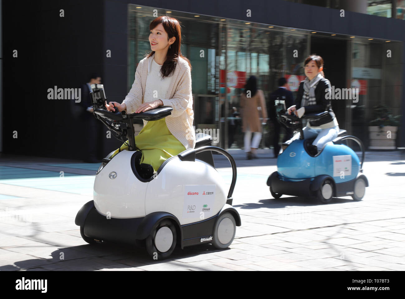 Tokyo, Japan. 18th Mar, 2019. Models demonstrate Japanese robot company Tmsuk personal mobility 'Rodem' in Tokyo on Monday, March 18, 2019. NTT Docomo, Mitsubishi Estate and Tmsuk started a field test to drive Rodem on the road in Marunouchi for sightseers. Credit: Yoshio Tsunoda/AFLO/Alamy Live News - Stock Image