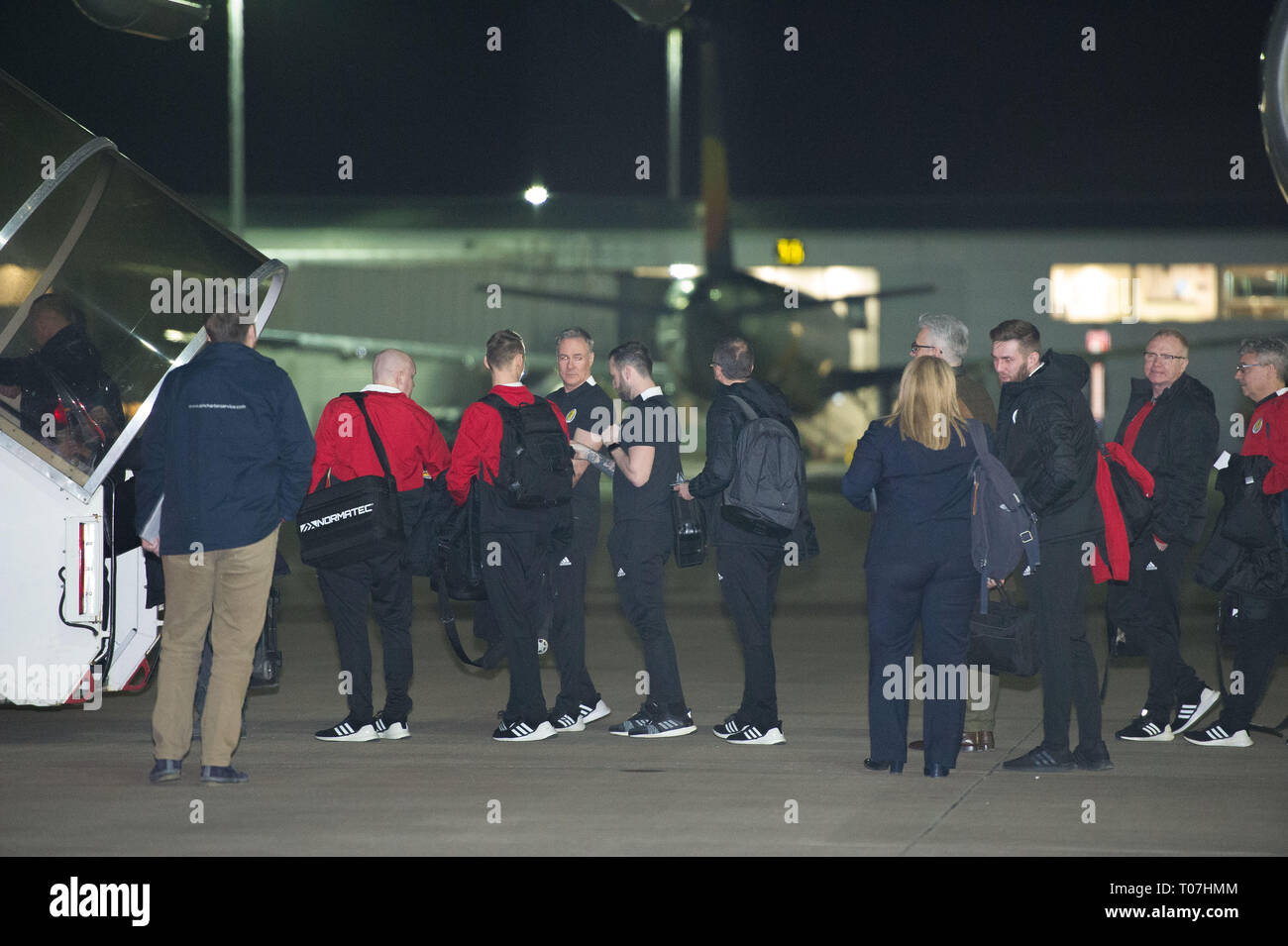 Glasgow, UK. 18 March 2019. Scottish Football Coach, James McFadden (7th from right) and Manager, Alex McLeish (2nd from right) and the Scotland Football Team seen boarding their luxury jetliner private aircraft in the early hours seen  at Glasgow Airport moments before departing for Kazakhstan to play a game on Wednesday.  The flight was due to take off at 11pm, however due to an unforeseen problem where the pilot had to come out of the flight deck and onto the tarmac and speak with ground crew, the flight eventually took off in the early hours of today. Credit: Colin Fisher/Alamy Live News - Stock Image