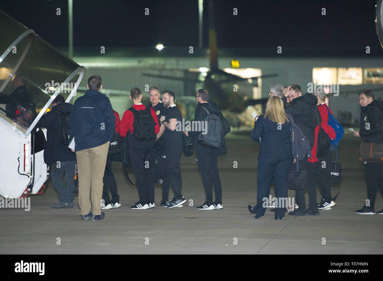 Glasgow, UK. 18 March 2019. Callum Patterson (7th from right) and Peter Grant (extreme right) and the Scotland Football Team seen boarding their luxury jetliner private aircraft in the early hours seen  at Glasgow Airport moments before departing for Kazakhstan to play a game on Wednesday.  The flight was due to take off at 11pm, however due to an unforeseen problem where the pilot had to come out of the flight deck and onto the tarmac and speak with ground crew, the flight eventually took off in the early hours of today. Credit: Colin Fisher/Alamy Live News - Stock Image