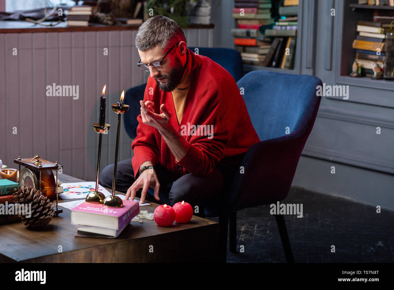 Bearded fortune-teller having some difficulties while working at home - Stock Image