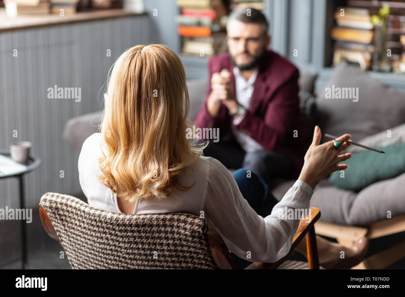 Therapist wearing white blouse giving personal assistance to businessman - Stock Image