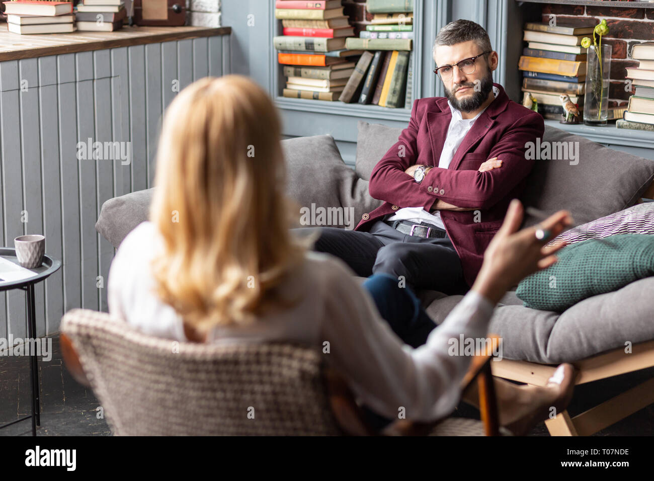 Bearded rich man listening to his personal therapist attentively - Stock Image