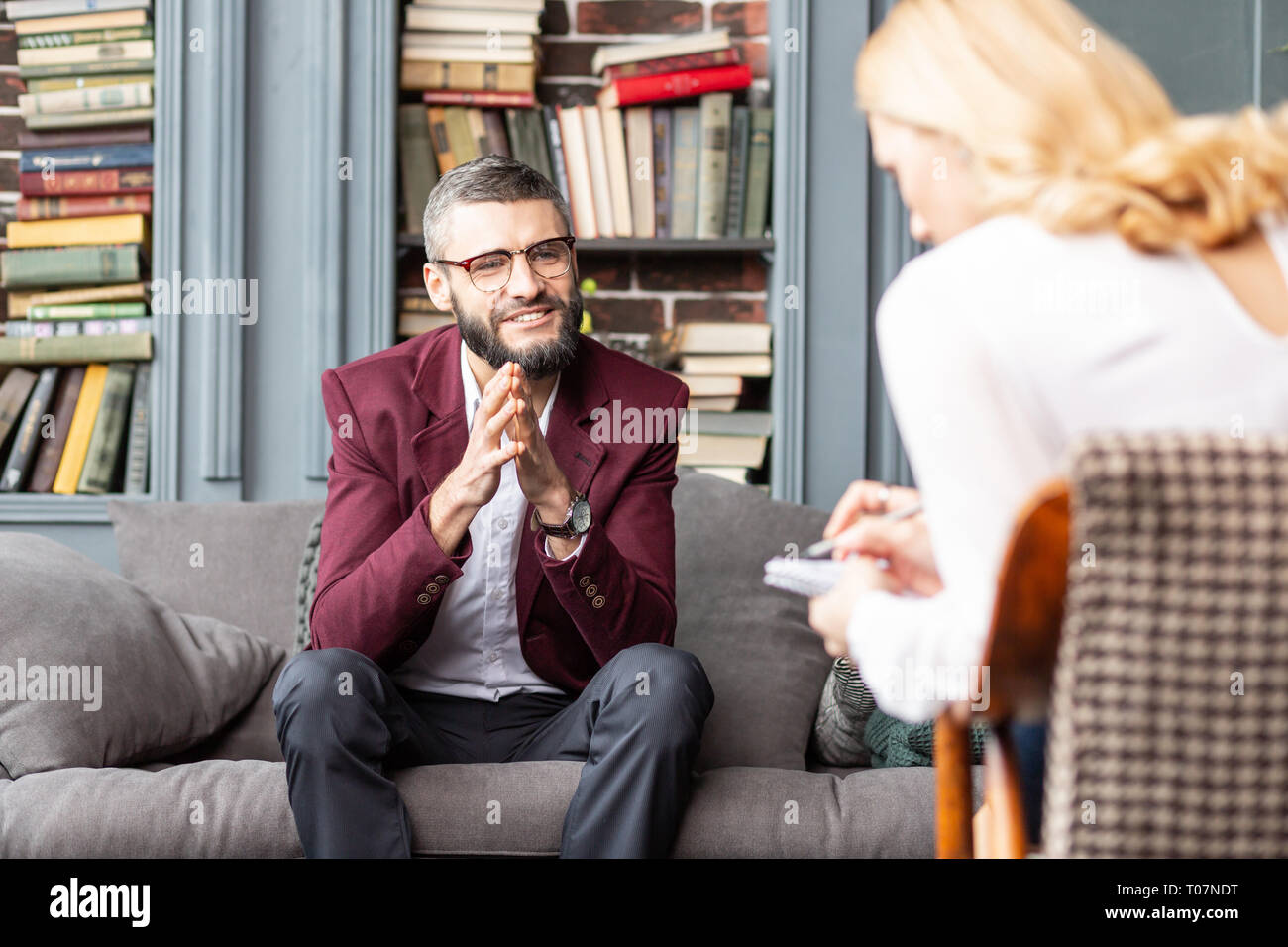 Bearded man smiling after successful talk with private therapist Stock Photo