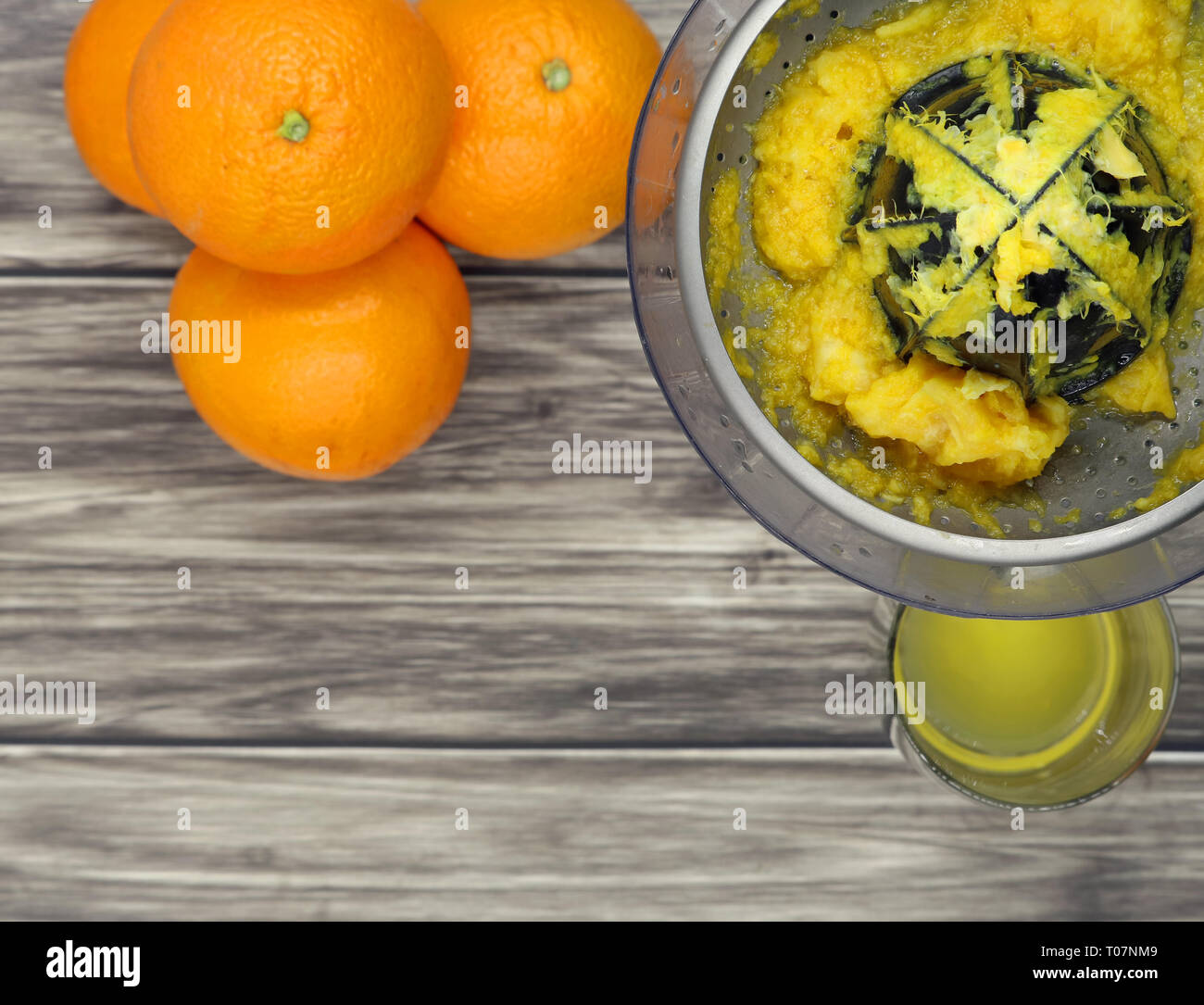top view of oranges, a juicer and a glass of juice on wooden background, copy space - Stock Image
