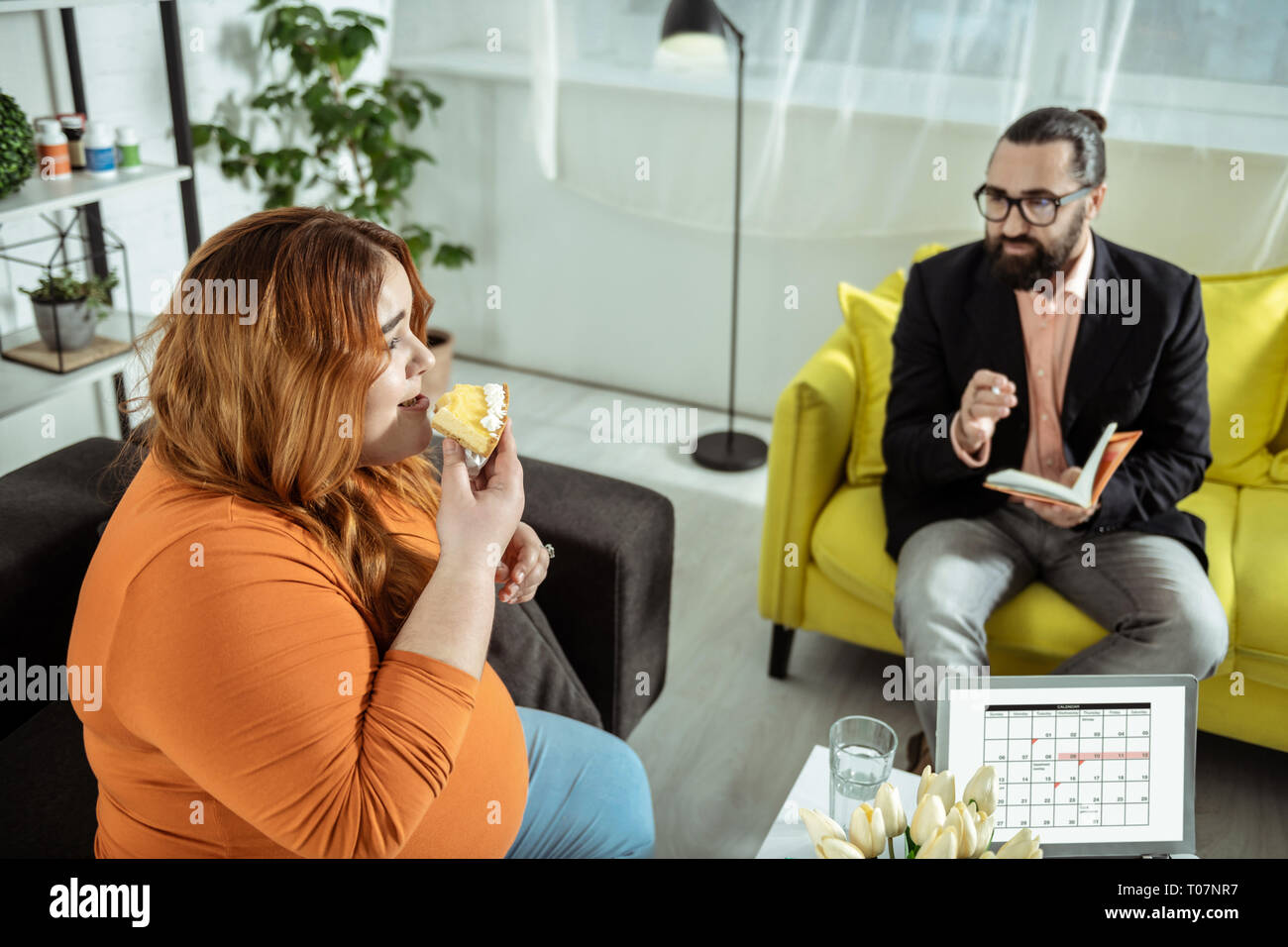 Emotional red-haired woman having serious eating disorder - Stock Image