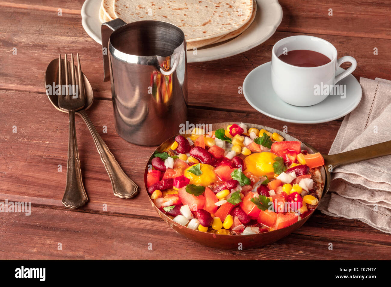 Mexican breakfast. Huevos rancheros, the fried eggs, with the pico de gallo salad, hot chocolate, and tortillas on a dark rustic wooden table - Stock Image