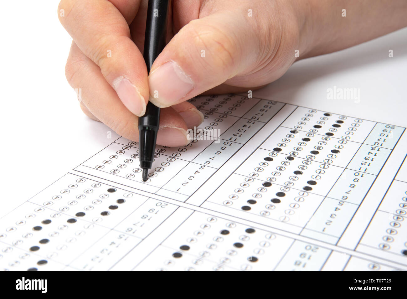 Man is filling OMR sheet handing with pen. - Stock Image
