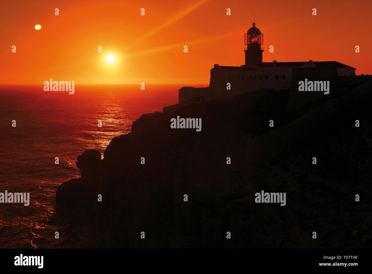 Romantic sunset at rocky coast with lighthouse Stock Photo