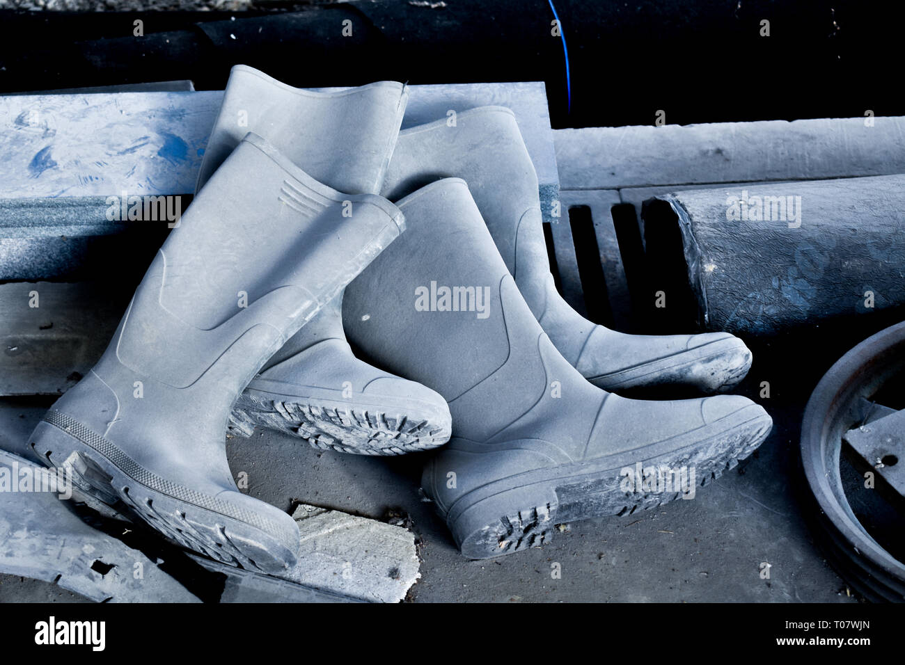 Old forgotten working rubber boots, discarded on the floor, factory dirty floor - Stock Image