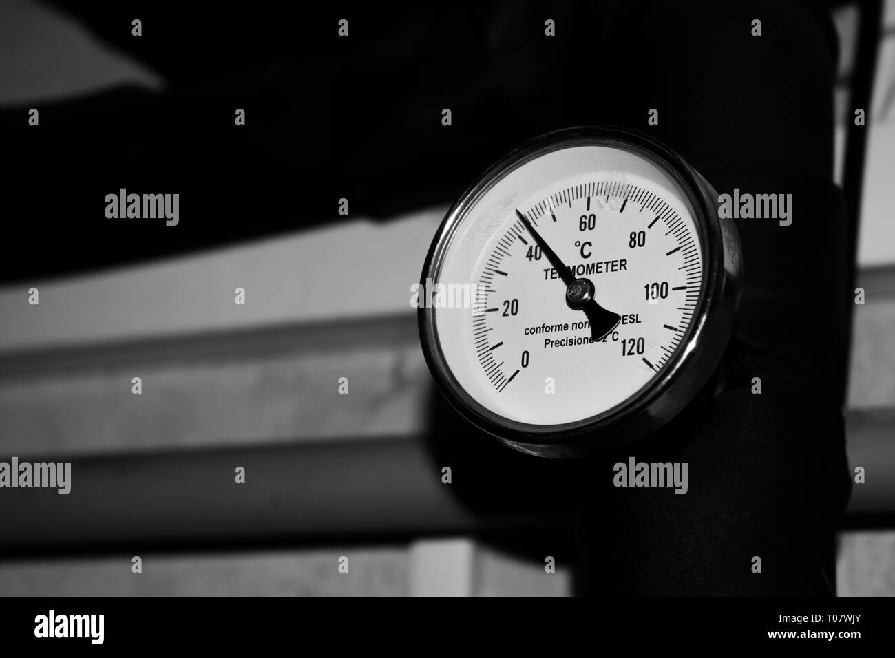 Pressure spring dial thermometer metering temperature of water in heating pipes, black and whites - Stock Image