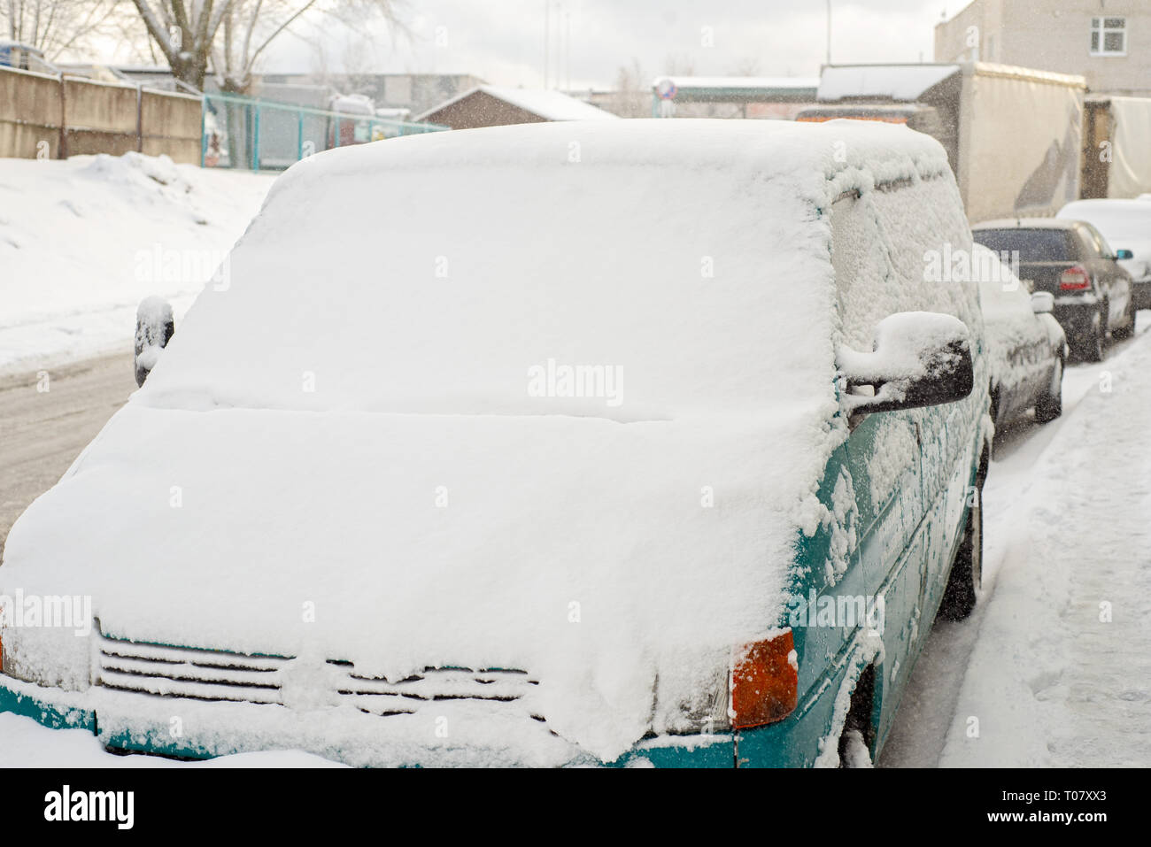 Green car is covered with snow parked near the street Stock Photo