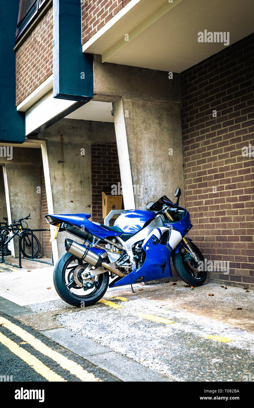 Blue and white sports motorbike parked on a path next to a modern building in Newcastle upon Tyne, Tyne and Wear, UK Stock Photo