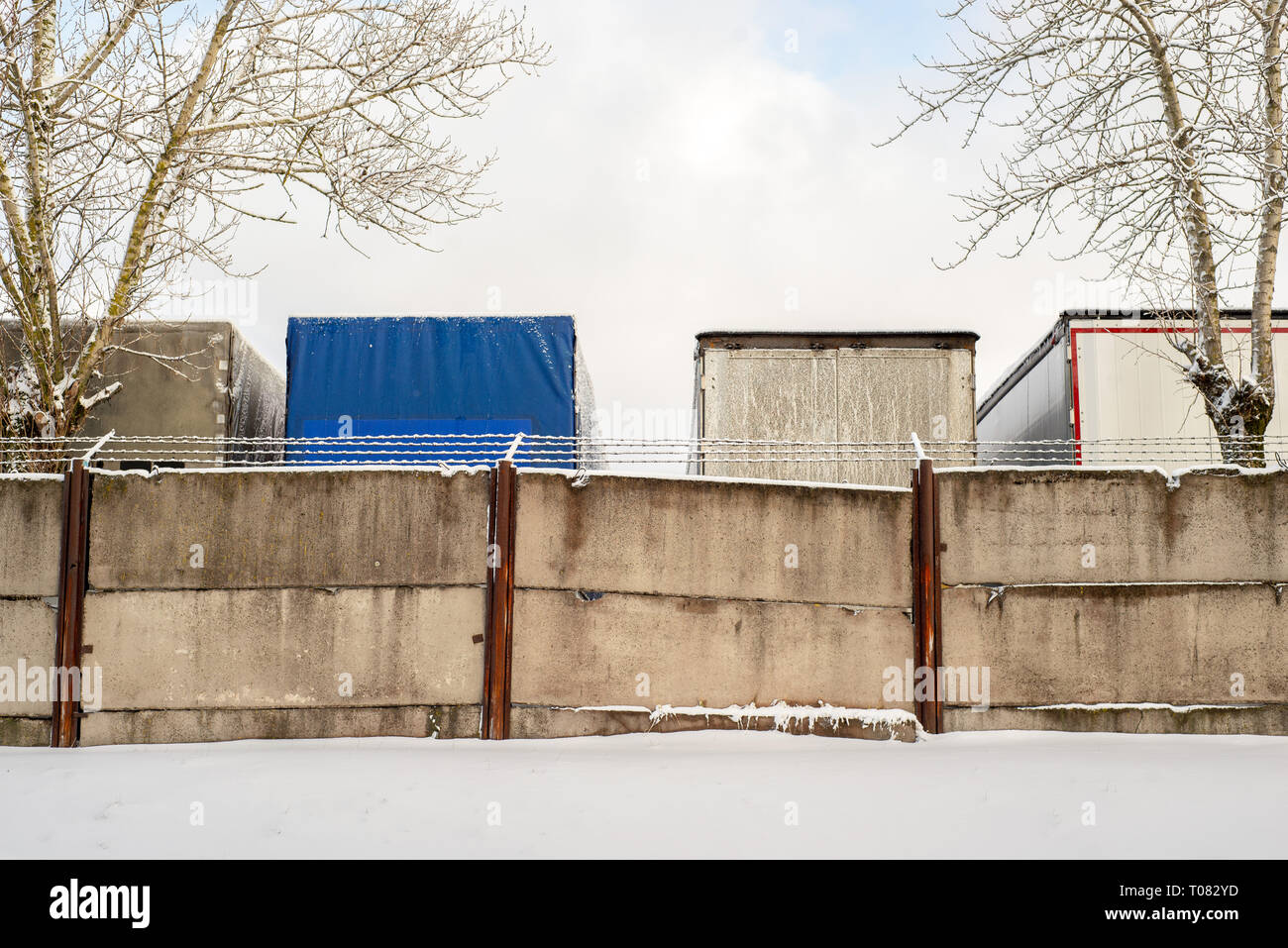Trucks standing behind the fence wall in winter Stock Photo