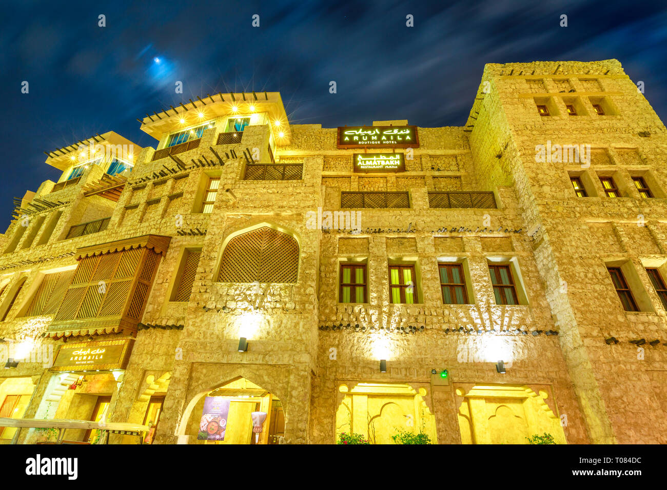 Doha, Qatar - February 18, 2019: facade of historic building at Souq Waqif in traditional Qatari architectural style at night. The souq is considered Stock Photo