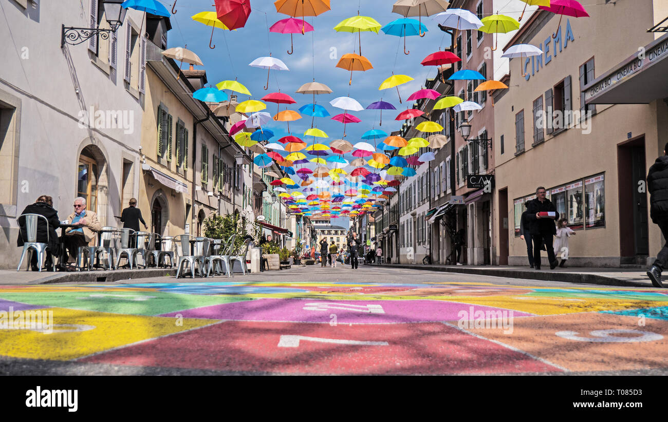 A modern brightly colored street art installation in the town of Geneva, Switzerland. Brightly colored umbrellas hang above a modern urban street. - Stock Image
