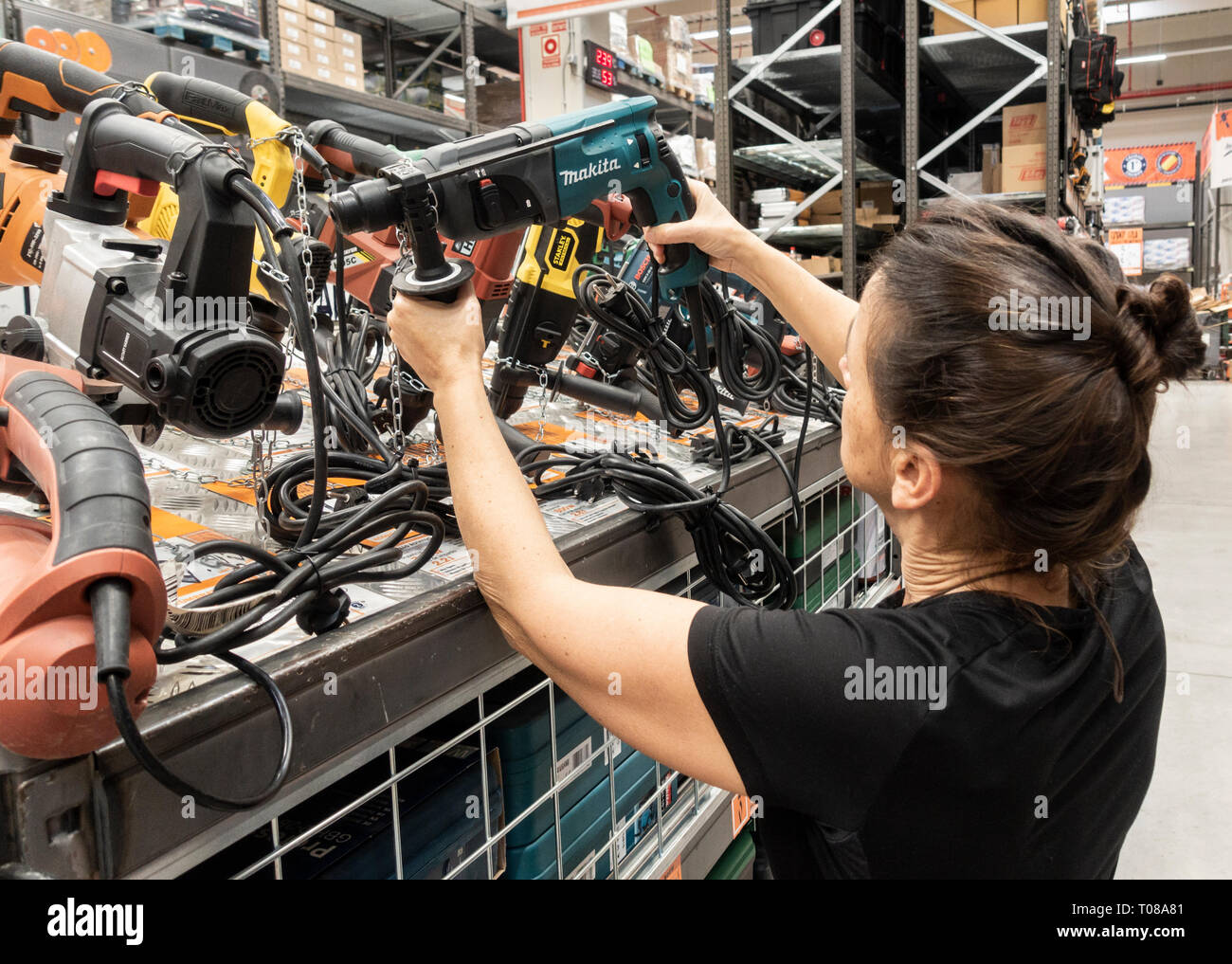 Mature woman holding power tool in DIY store. - Stock Image