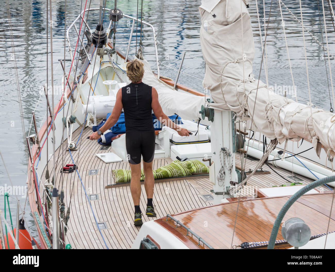 Sailor skipping/working out on large yacht in marina. - Stock Image