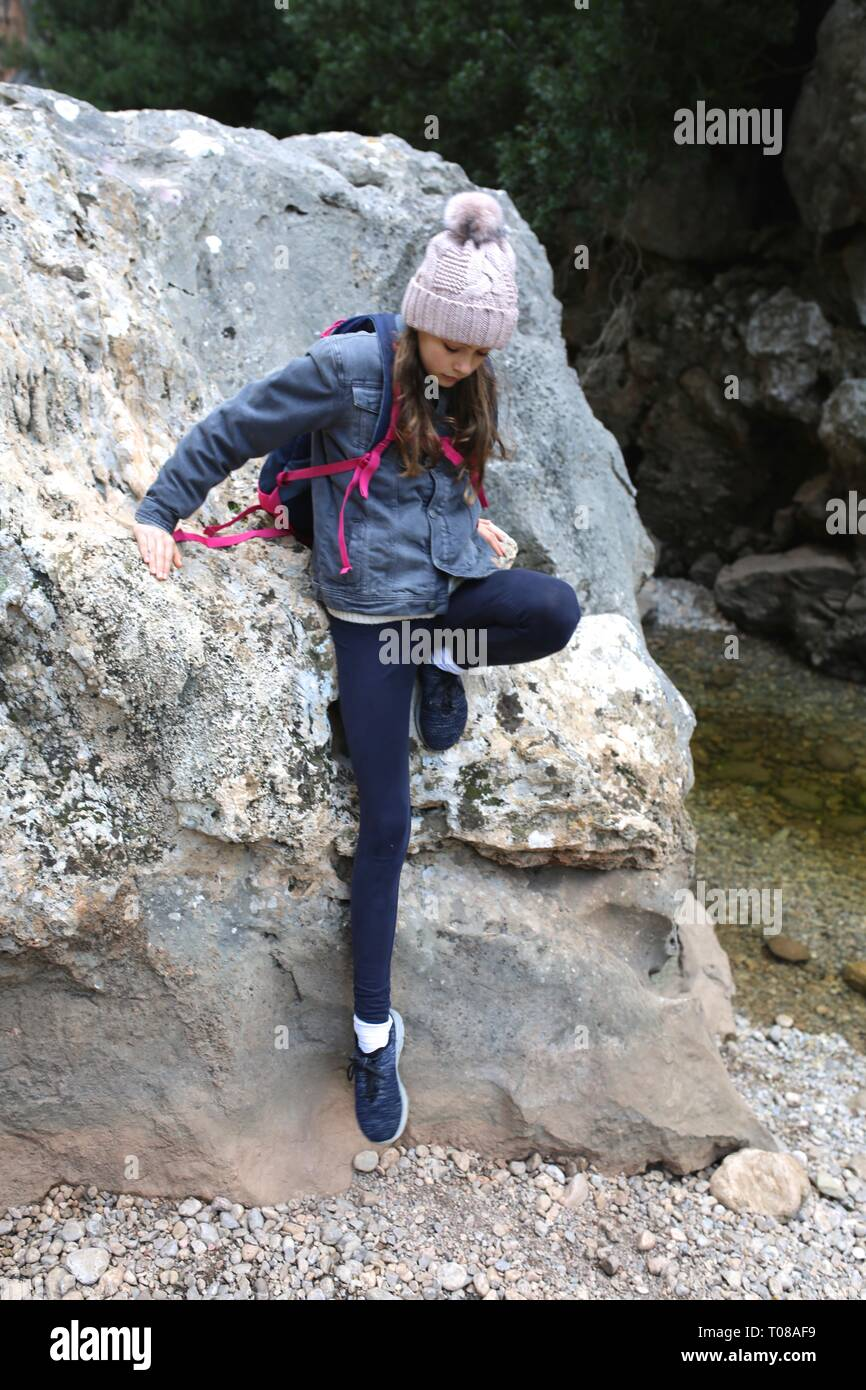 Pretty young girl with beanie and backpack climbing rock on a hike - Stock Image